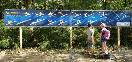 Kinder vor dem Banner mit Gorodki Spielregeln