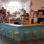 Küche hinter einem türkis gestrichenem Tresen