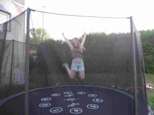 Ein Mädchen hüpft auf einem Trampolin