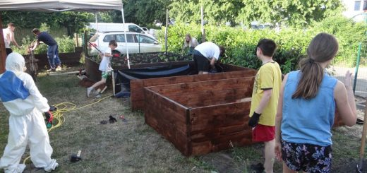 Kinder und Betreuer bauen Hochbeete