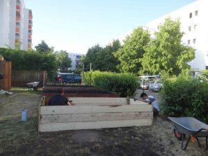Zwei M#änner imprägnieren Holzlatten für Hochbeete