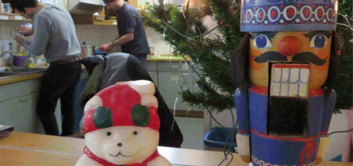 Weihnachtskerze in Bärchenform und ein Nussknacker vor einem Weihnachtsbaum