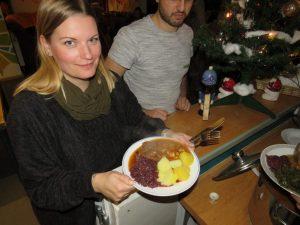 Betreuerin Peggy hält einen Teller mt Rotkohl, Kartoffeln und Gulasch in der Hand