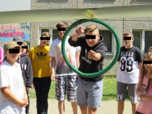 Ein Junge zielt mit einem Gummi auf einen Plastikring