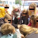 Kinder und Betreuer stehen im Kreis um einen Tisch herum und gucken auf einen Zettel