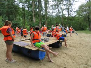 Kids mit Schwimmwesten bereiten sich am Strand auf eine Floßtour vor
