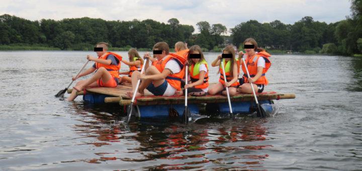 Kids paddeln mit einem selbstgebauten Floß auf der Havel