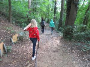 Mädchen mit Brennholz auf einem Waldweg