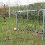 Ein Fußball vor einem Fußballtor auf einer Wiese