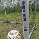 Ein Ball liegt an einem Torpfosten mit dem Logo JFE-Mikado