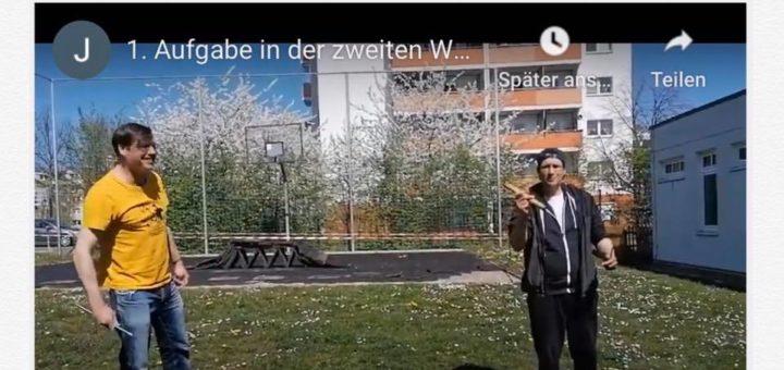 """Zwei Betreuer mit Holzstückchen in der Hand erklären die """"Weekly-Challenge""""-Aufgabe des Tages"""
