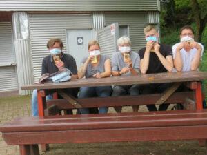BetreuerInnen mit Masken und Trinkpäckchen auf einer Bank