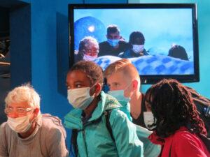 Ein männlicher und drei weibliche Reiseteilnehmer schauen mit Maske in eine Kamera