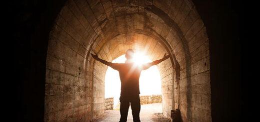 Eine Person steht am lichtdurchfluteten Ende eines dunklen Tunnels