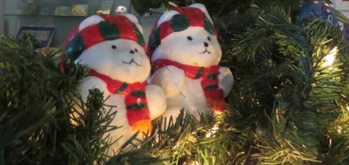 Zwei Weihnachtsbärchen im Adventskranz mit weihnachtlicher Beleuchtung.