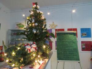 Weihnachtsbaum mit Deko und Beleuchtung und ene Schautafel mit Iformationen zur Adventslotterie