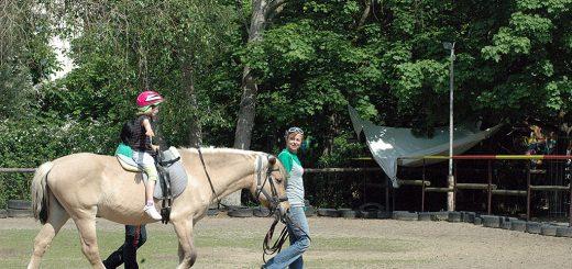 Mandy Kunkel führt Pferd mit reitendem Kind